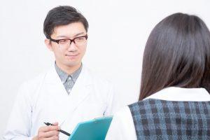 頭が揺れる症状を医師に話す女性